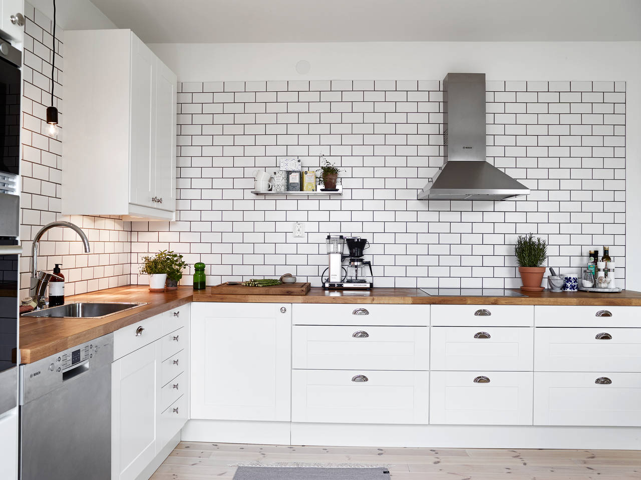 a white tiles black grout kind of kitchen